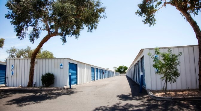 A row of outdoor storage units with blue doors