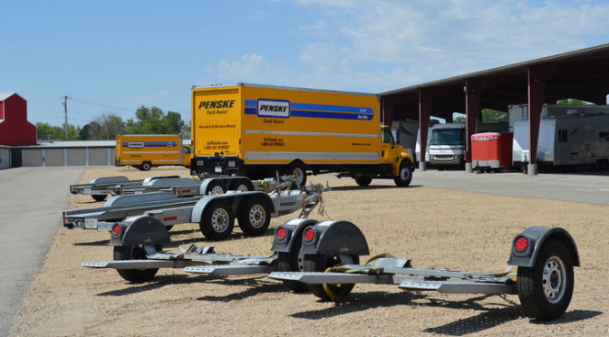 Outdoor parking area with moving trucks, RVs, and spare trailers