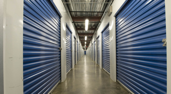 A long well lit hallway of indoor storage units with blue doors