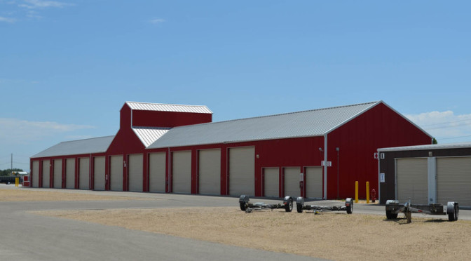 A distance view of an outdoor storage unit facility with differ sized units and an area for parked trailers