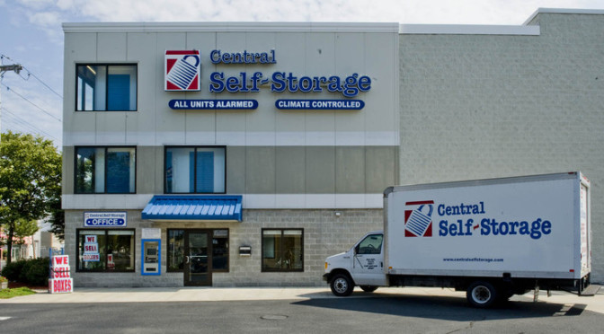 Exterior view of a Central Self Storage facility with a moving truck parked outside