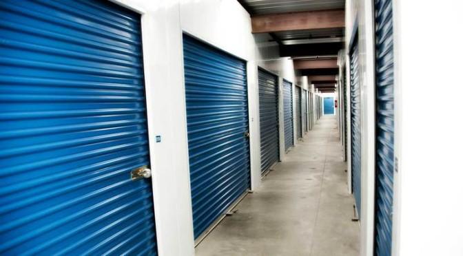 A clean well lit hallway of indoor storage units with blue doors and door locks