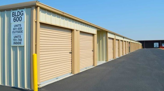 Outdoor row of storage units with orange doors in a clean environment