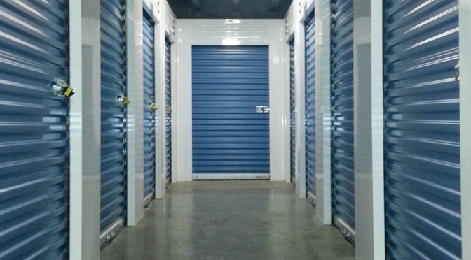 Clean, well lit hallway of indoor storage units with blue doors and locks