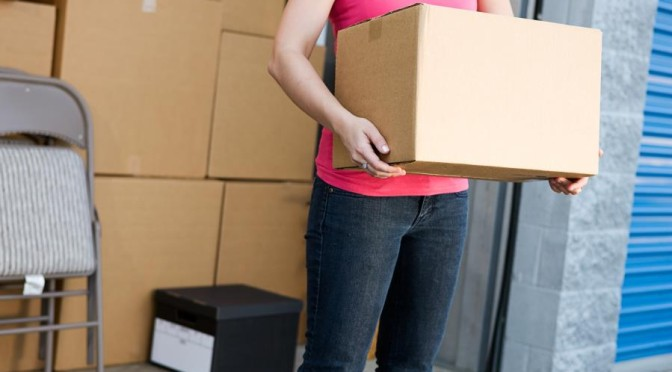 woman with box outside of storage unit