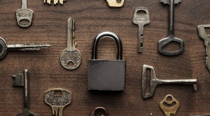single padlock with a bunch of keys on wood surface