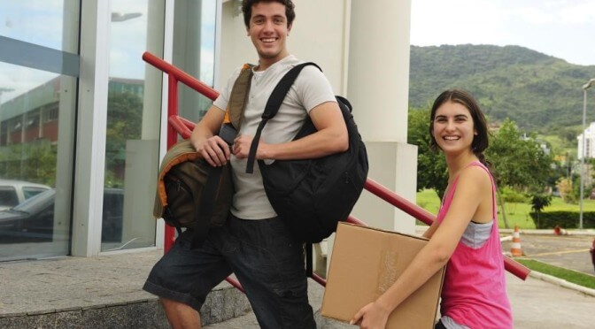 Young couple moving into dorm room smiling at camera