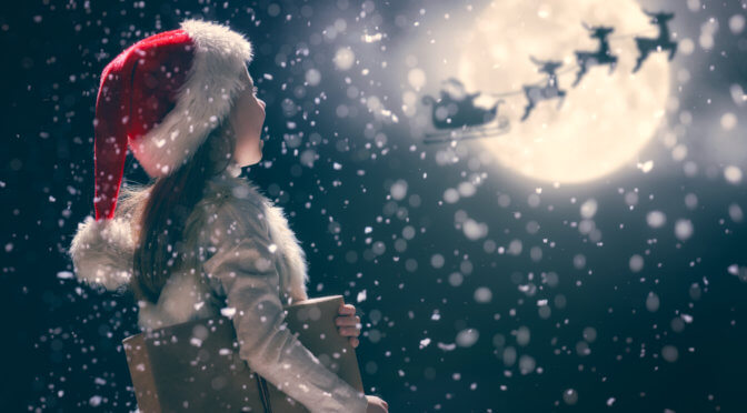 little girl looking up at santa's sleigh being pulled by reindeer in the snow