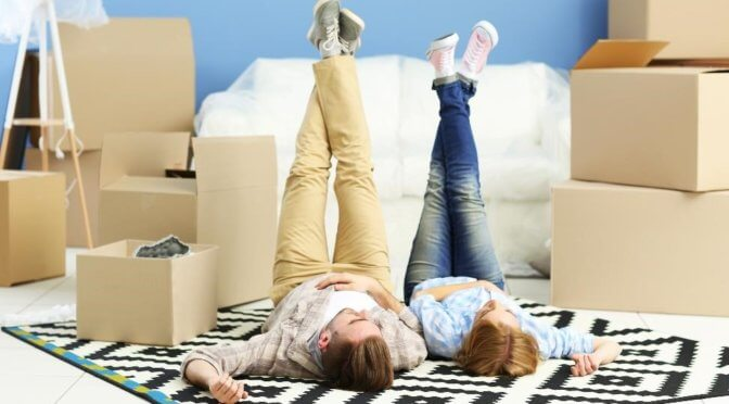 a couple lying side by side on a rug with moving boxes around them