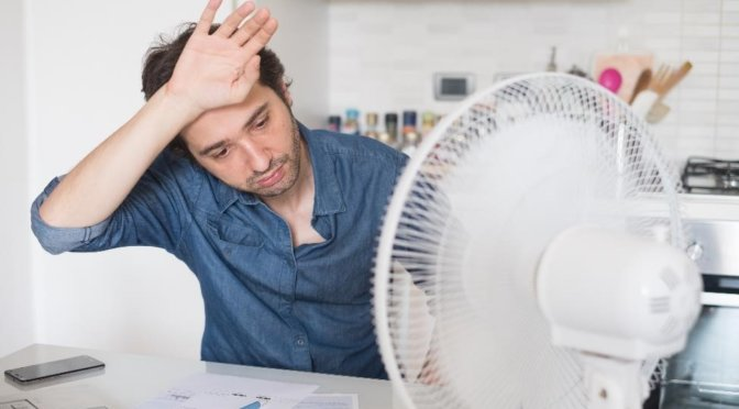 dark-haired man wearing blue shirt wiping sweat from forehead while sitting in front of a fan