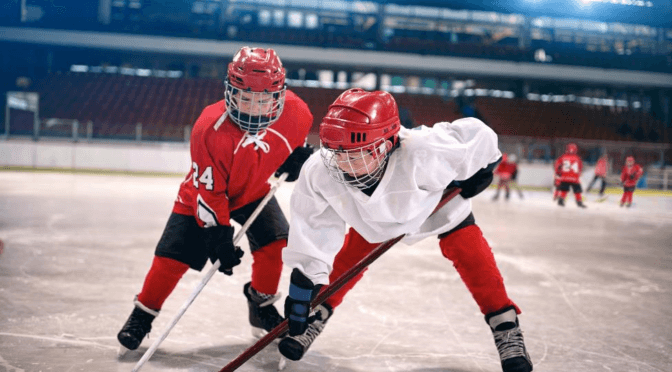 Two youth hockey players fighting for the puck